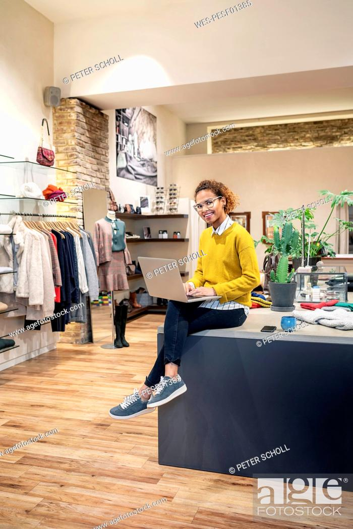 Stock Photo: Young woman working in fashion store, using laptop.
