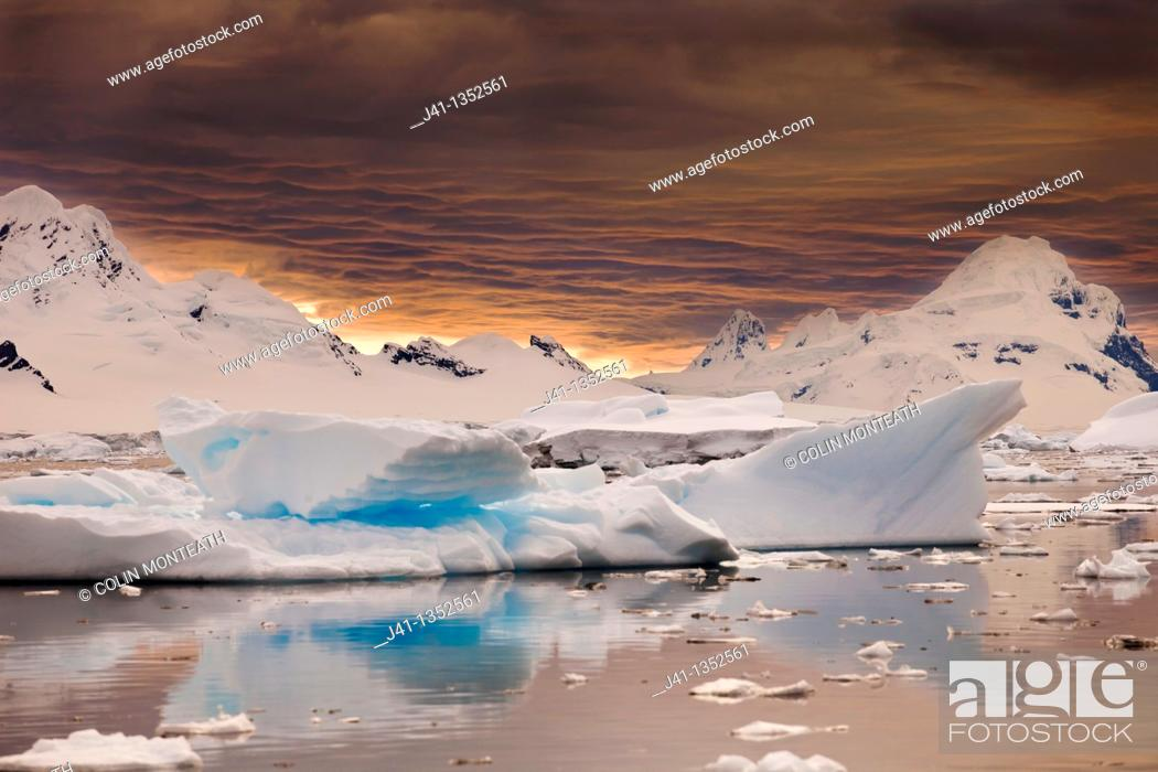 Imagen: Storm clouds gather at sunset over peaks around Wiencke Island, Neumeyer Channel, Antarctic Peninsula.