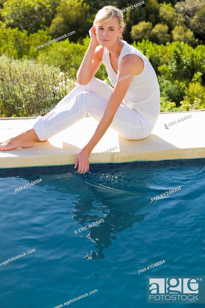 Stock Photo: Portrait of a woman sitting at the poolside.