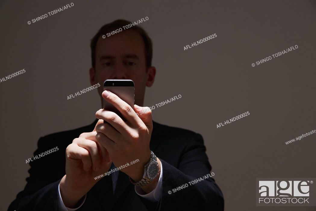 Stock Photo: Businessman in a suit with smartphone.