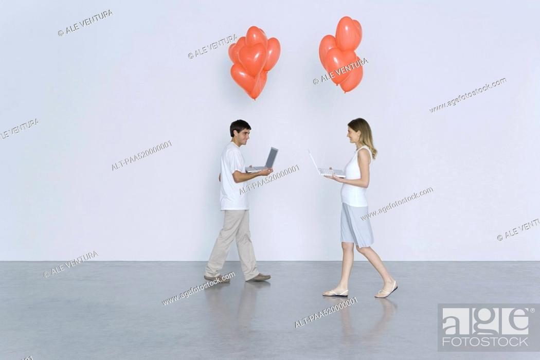 Stock Photo: Young man and woman walking toward each other, both carrying laptop computers and heart balloons.