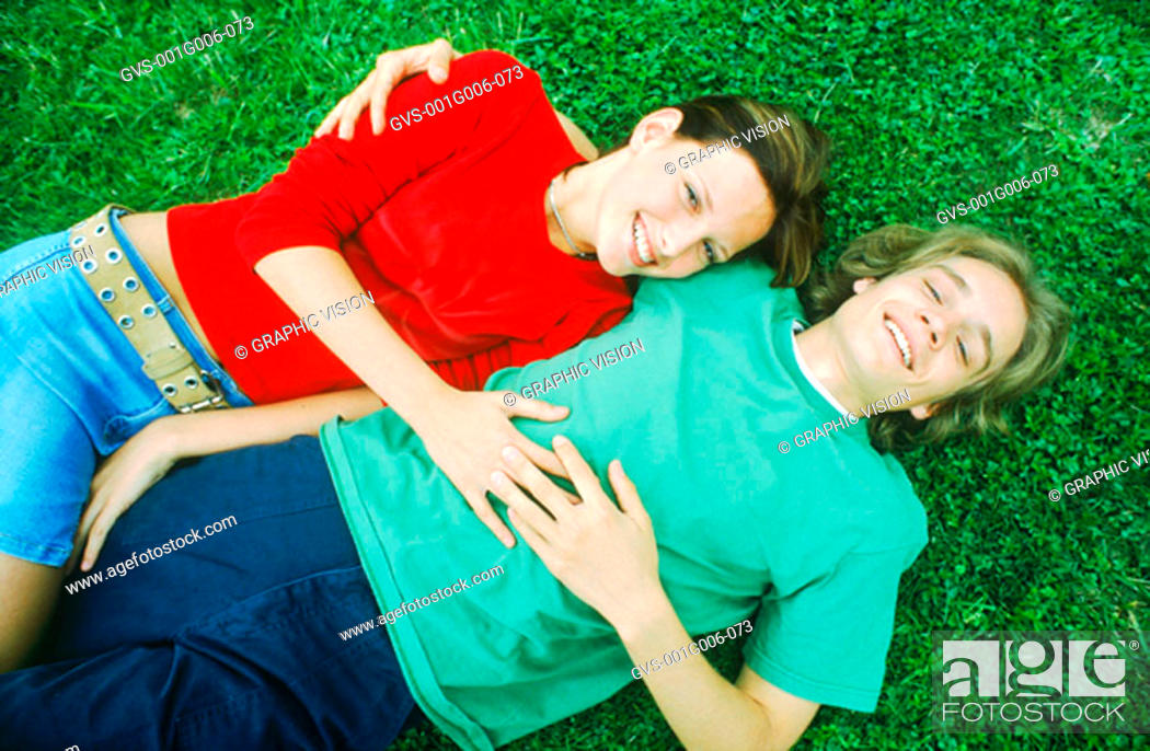 Stock Photo: Portrait of young couple lying on the grass holding each other.