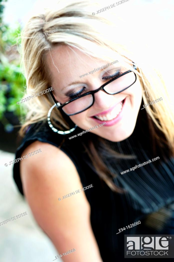 Stock Photo: Close in shot of a 31 year old blond woman wearing reading glasses with a flirty smile, eyes looking down.