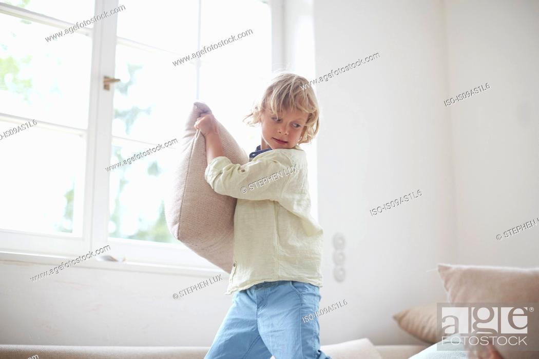 Stock Photo: Boy holding pillow preparing to throw.