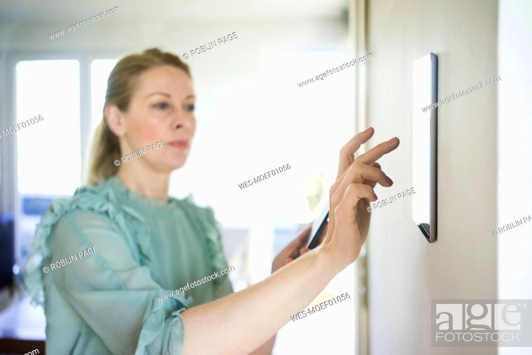Stock Photo: Woman adjusting digital tablet mounted on wall with smartphone.