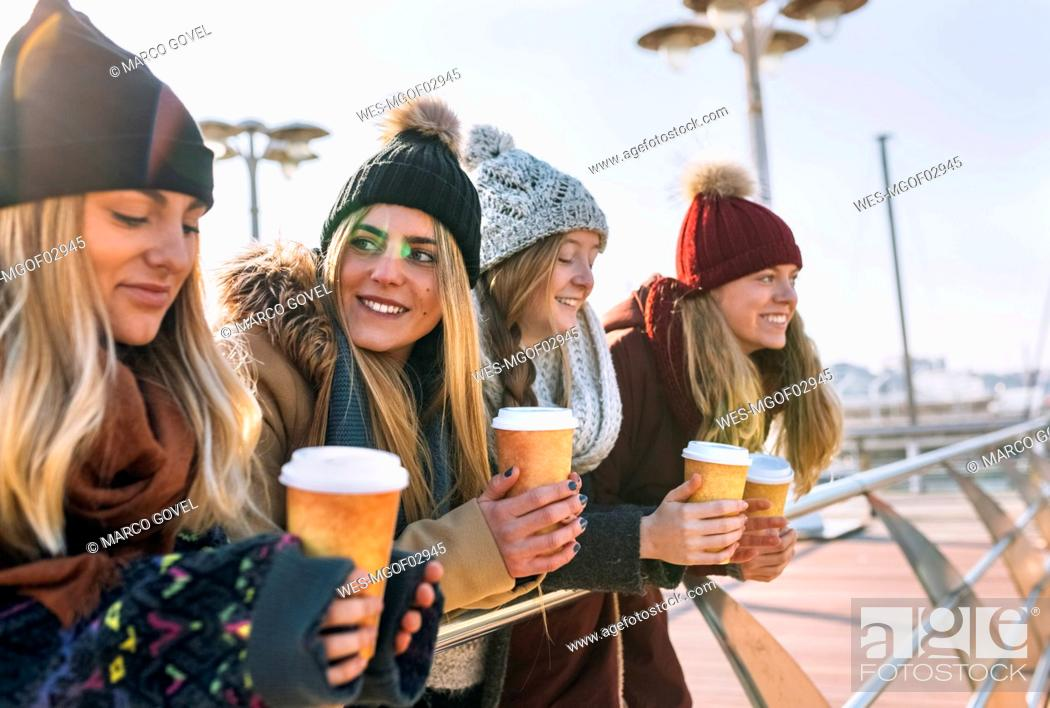Stock Photo: Four friends with coffee to go in winter.