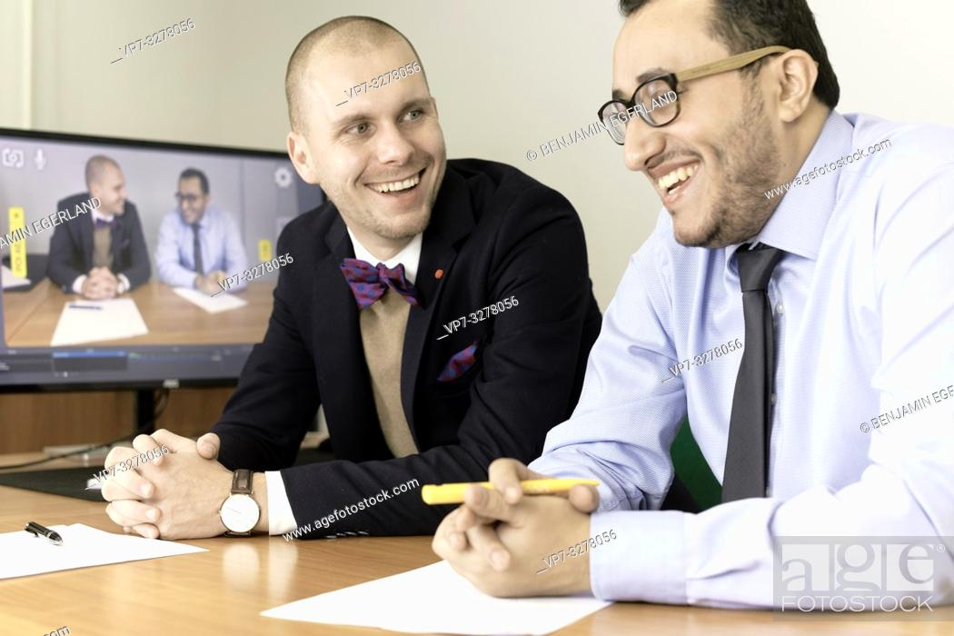 Imagen: laughing business men at conference, lawyers consulting at online live stream, in office, in Cottbus, Brandenburg, Germany.