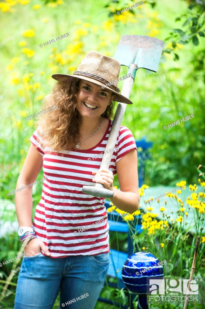 Stock Photo: Smiling young woman with straw hat and spade in a garden.