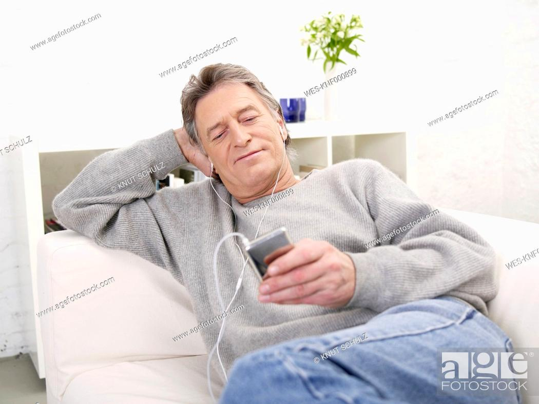 Stock Photo: Germany, Hamburg, Senior man listening MP3 player.