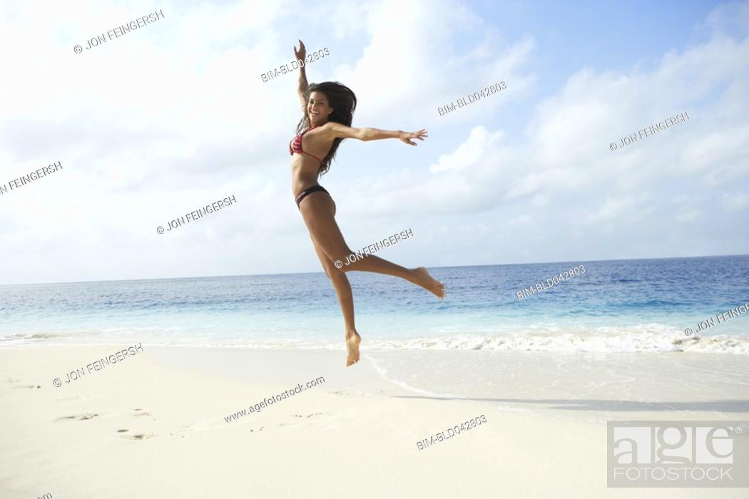 Stock Photo: South American woman jumping on beach.