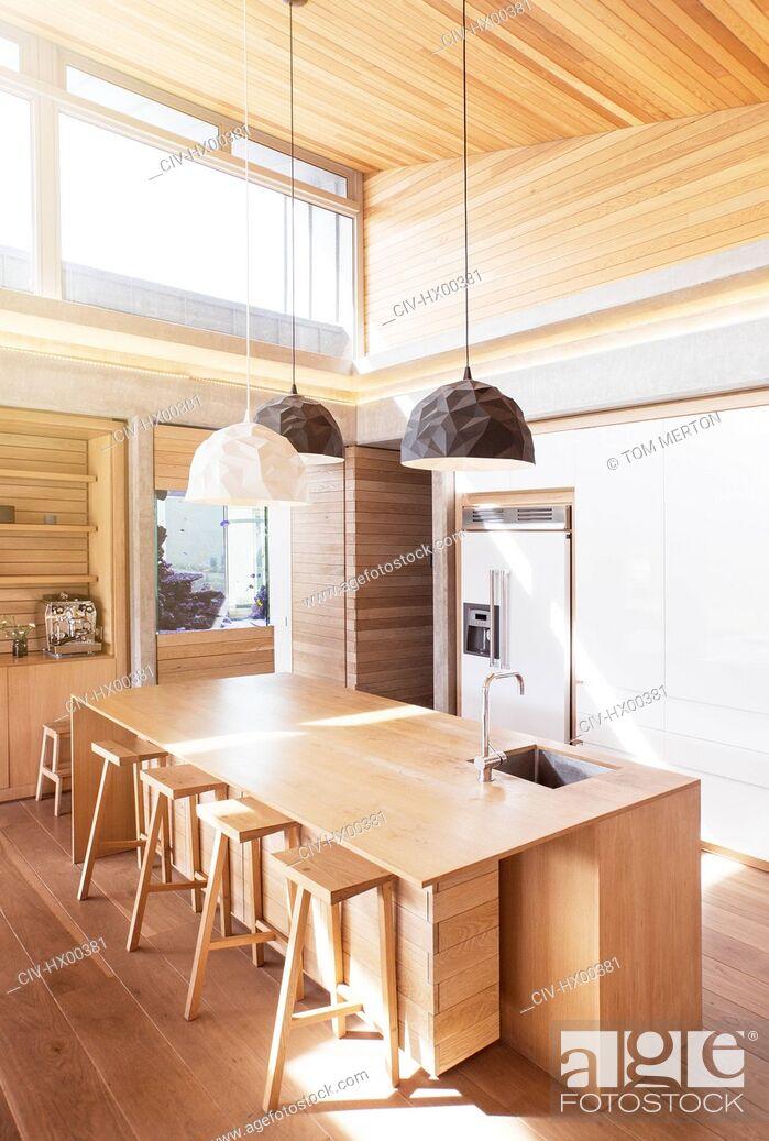 Stock Photo: Modern pendant lights hanging over wooden kitchen island.