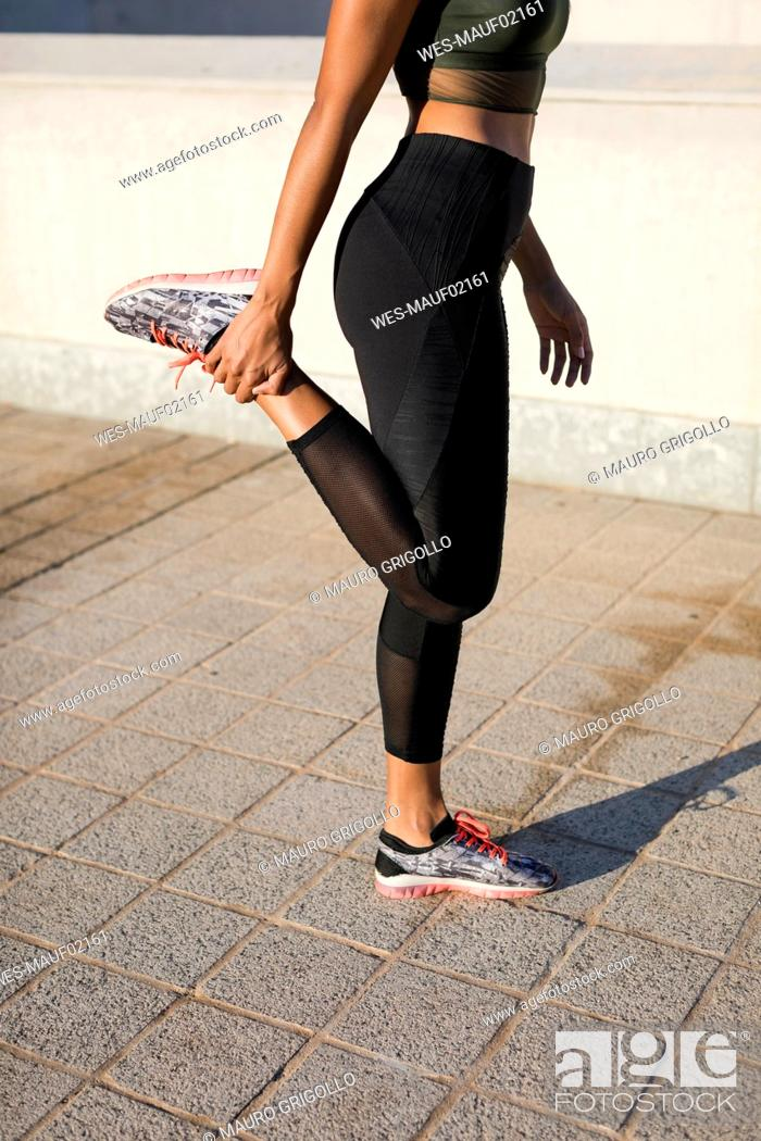 Stock Photo: Close-up of young woman doing stretching exercise in the city.
