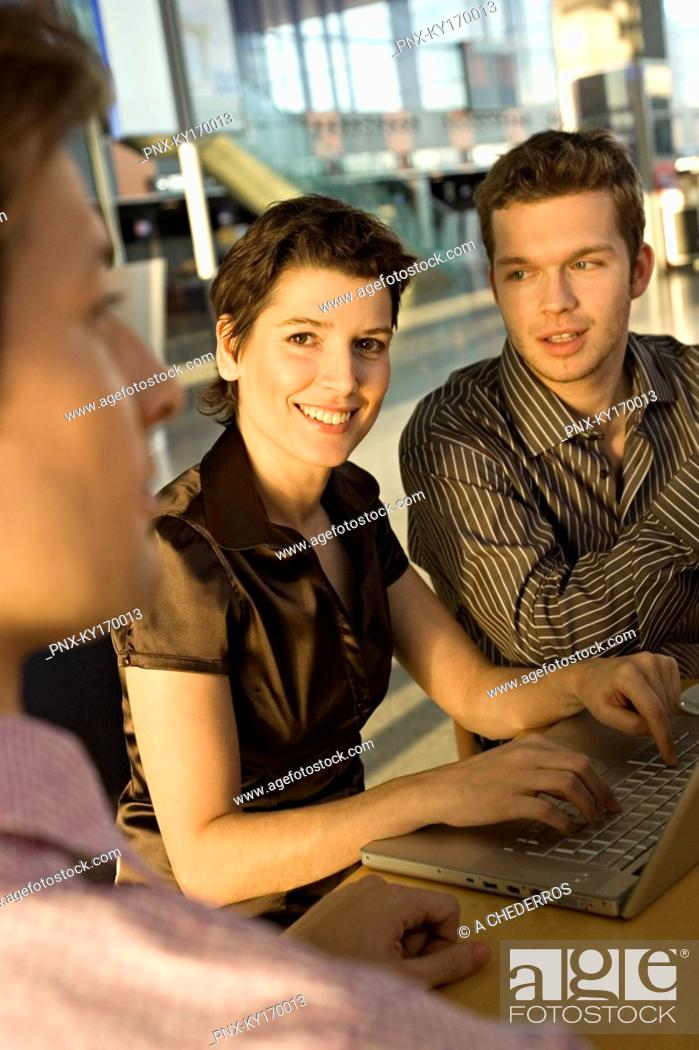 Stock Photo: Two businessmen and a businesswoman sitting in a meeting.