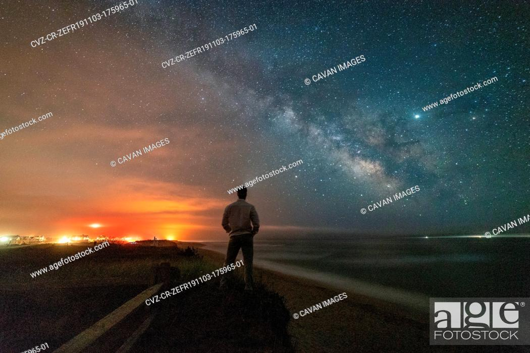 Imagen: Man looking out at Milky Way galaxy over the beach in Nantucket.