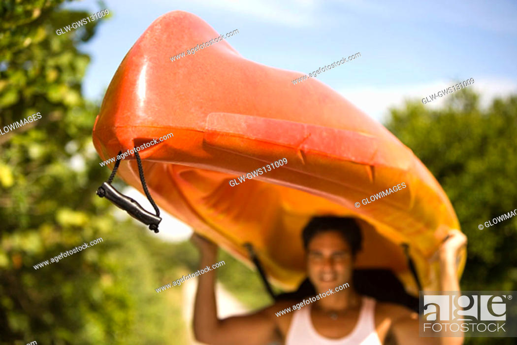 Stock Photo: Young man carrying a kayak on his head.