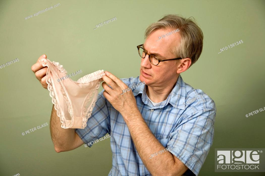 Stock Photo: Middle-age man holding up a pair of woman's panties.