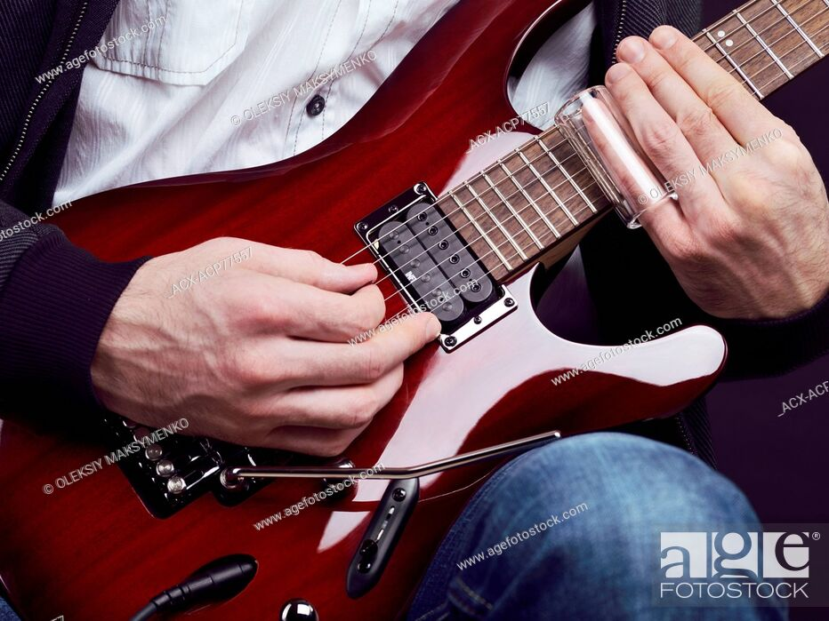 Stock Photo: Closeup of man hands playing red electric guitar with a slide.