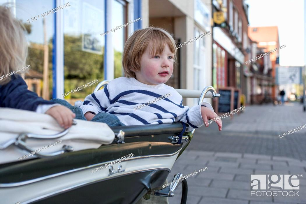 Stock Photo: England, Hertfordshire, Hitchin. A 3 year old boy in his perambulator.