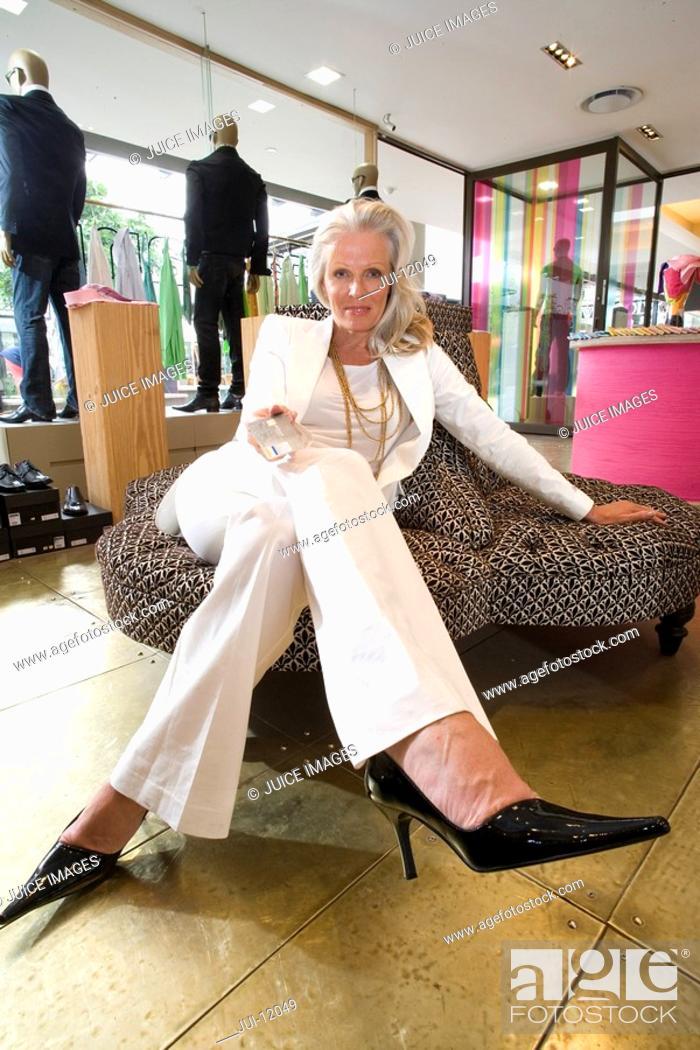 Stock Photo: Mature woman in shop, legs crossed, portrait.