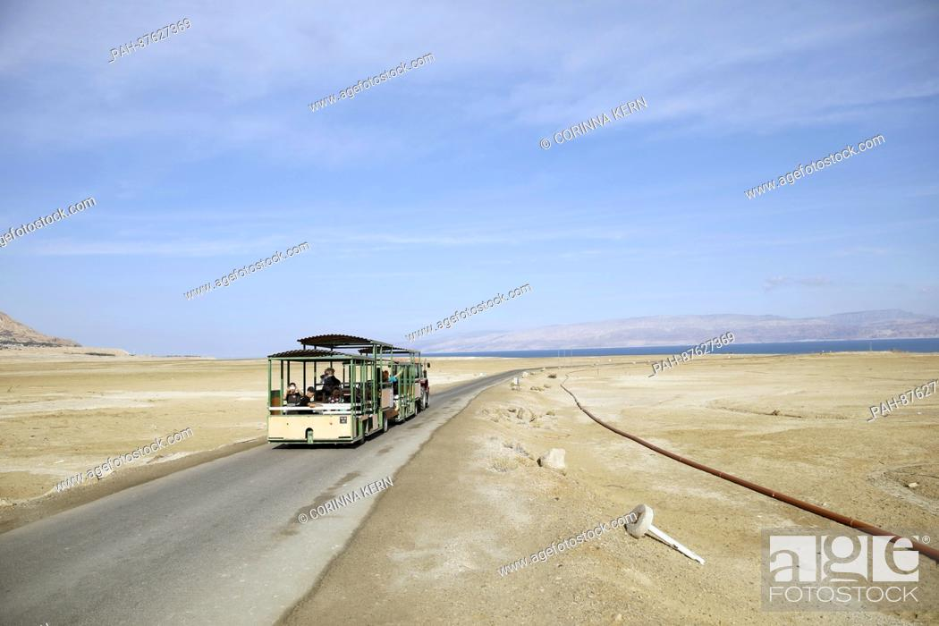 A bus drives along a road where the shore of the Dead Sea