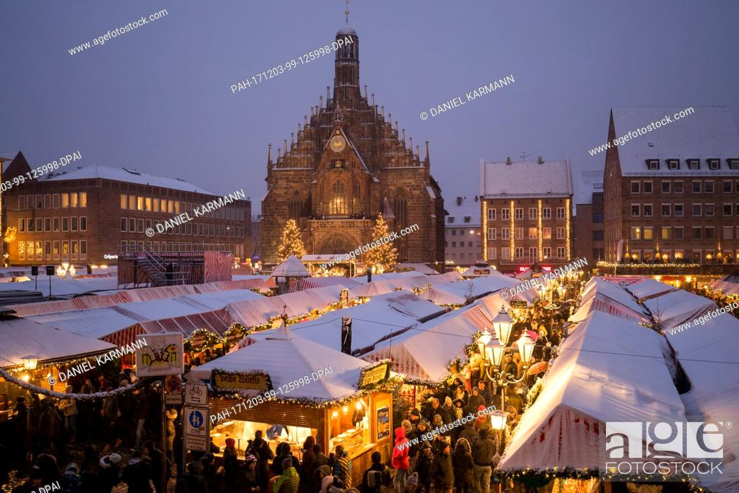 Stock Photo: Visitors walk in between the stands of the Christkindlesmarkt during snowfall in Nuremberg, Germany, 03 December 2017. Photo: Daniel Karmann/dpa.