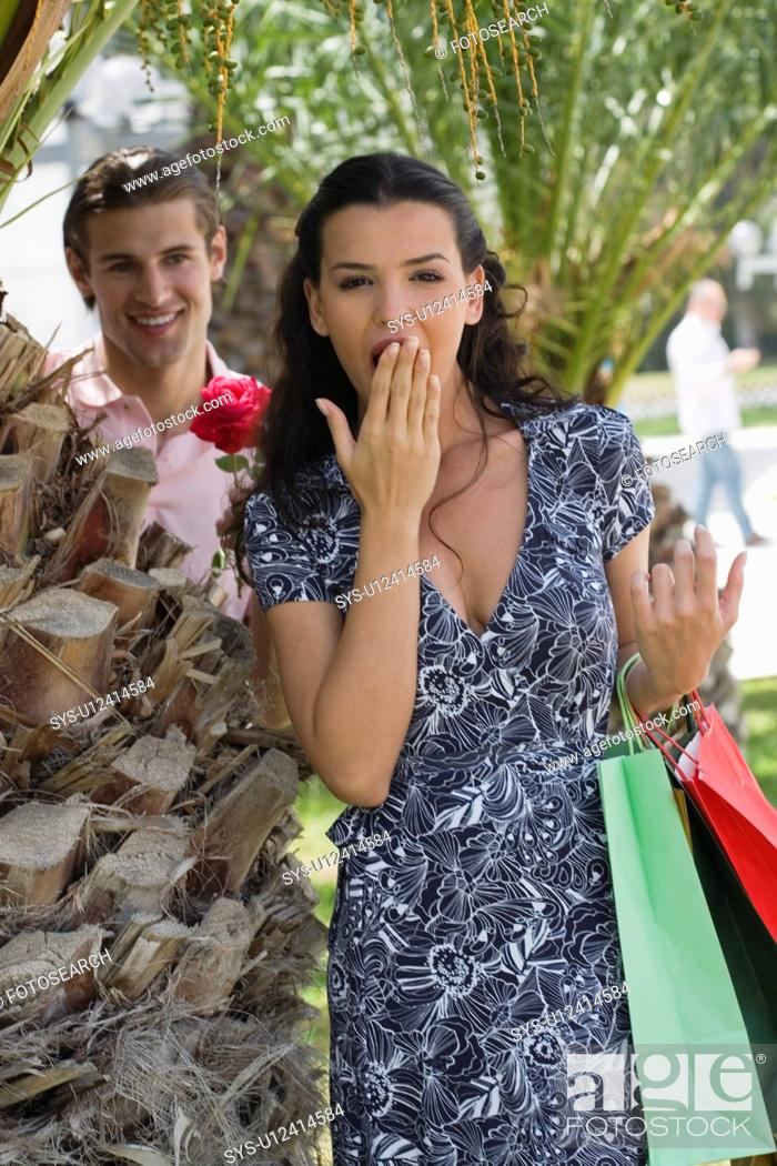 Stock Photo: Woman with shopping bags, man with rose.