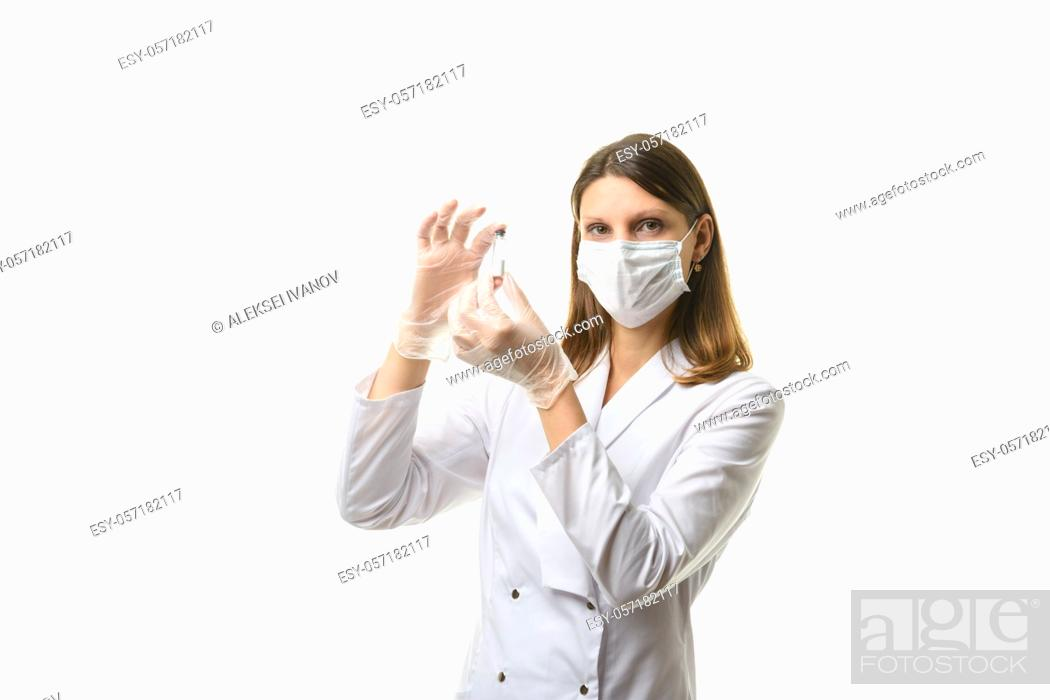 Stock Photo: Girl doctor stands with a glass test tube in her hands.