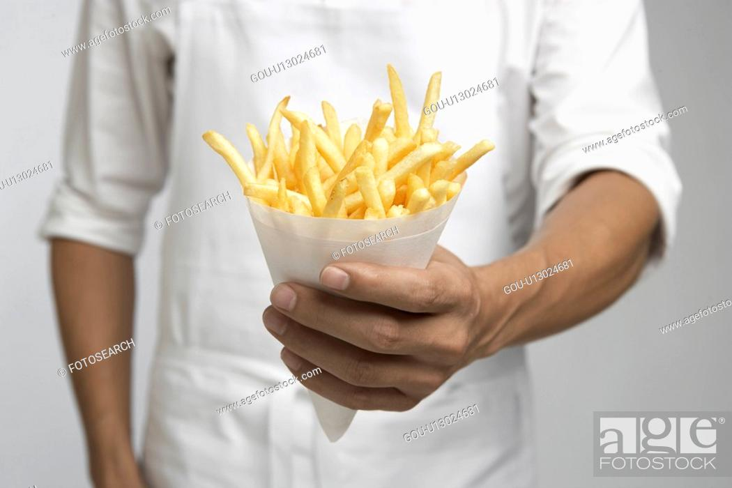 Stock Photo: Chef holding french fries (mid section).