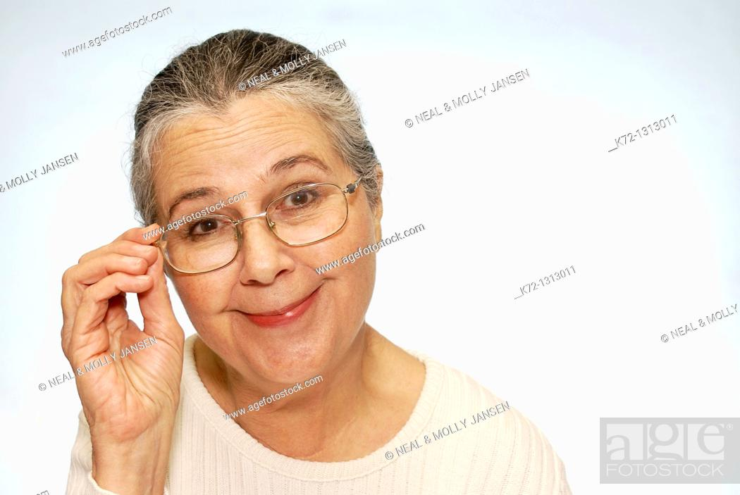 Stock Photo: Smiling older woman touching glasses on face.