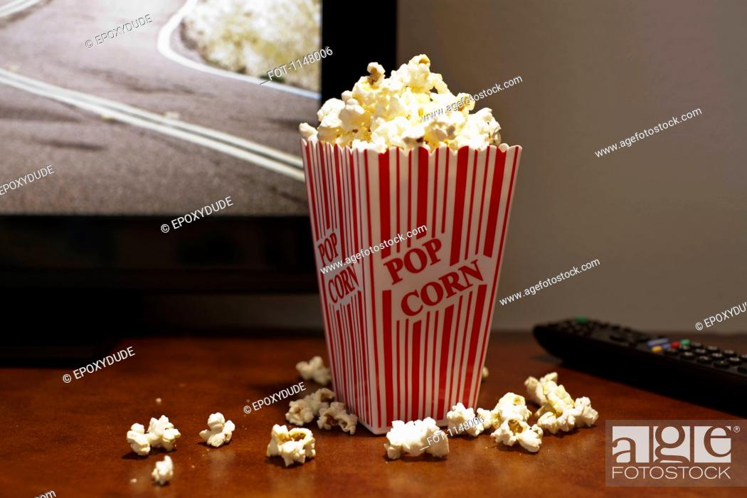 Stock Photo: A red striped carton of popcorn on a table in front of a flat screen TV.