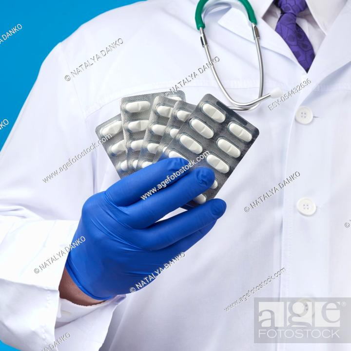 Stock Photo: male hand with blue sterile gloves holds a stack of pills in a blister, concept for drug treatment of diseases, blue background.