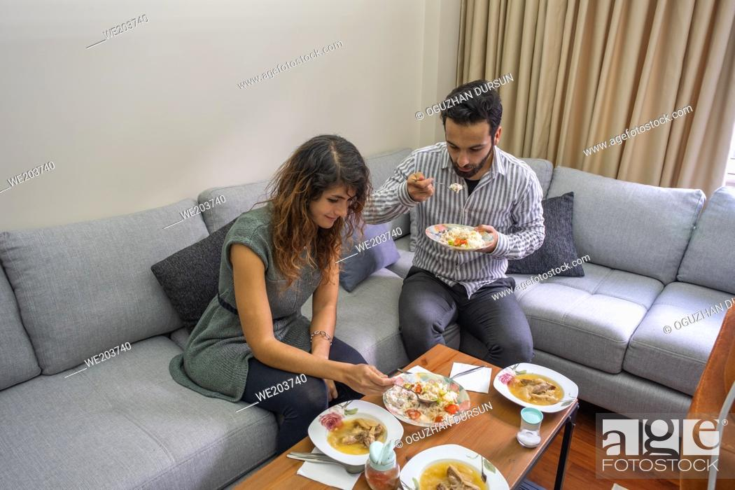 Imagen: handsome man and beautiful woman have lunch in living room lifestyle concept with copy space.