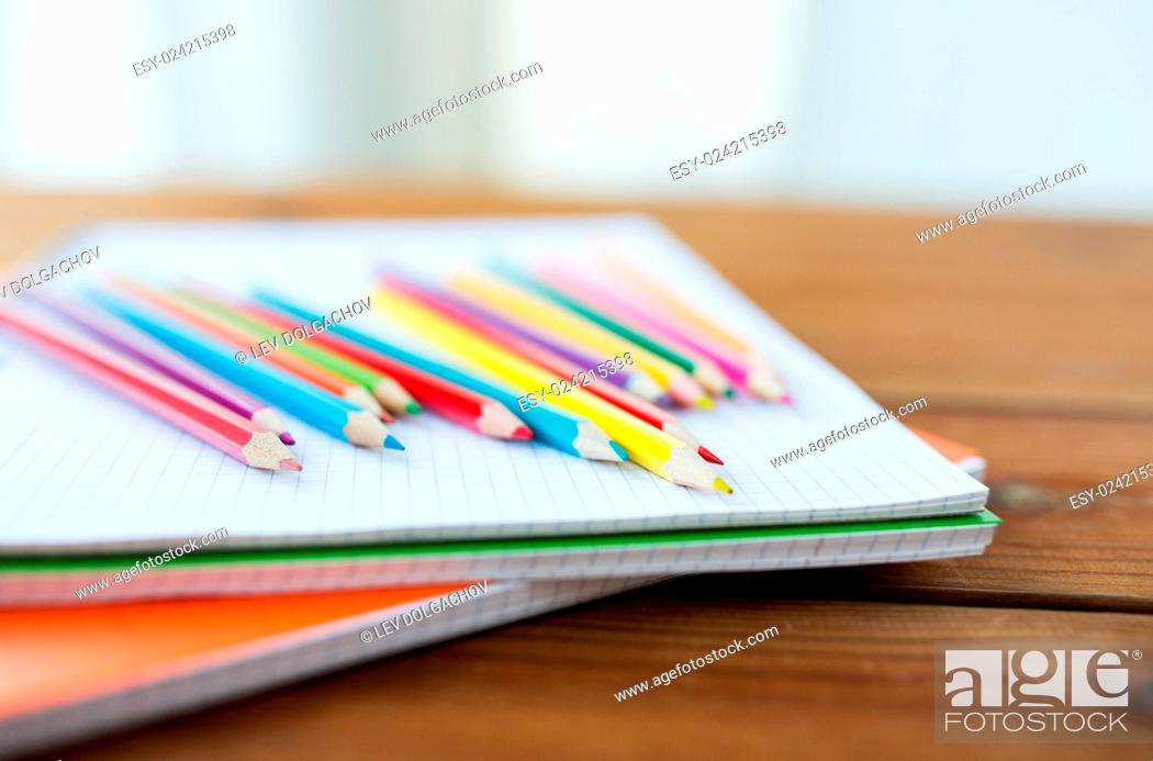 Stock Photo: art, school, education, drawing and object concept - close up of crayons or color pencils on notebook paper.