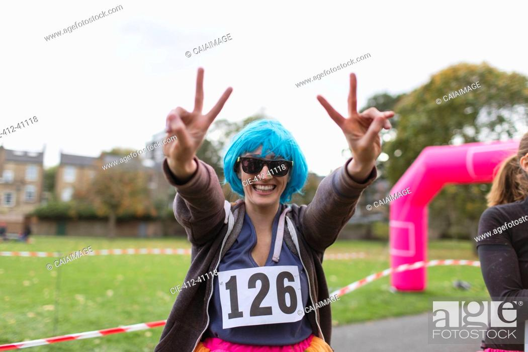 Photo de stock: Portrait enthusiastic female runner in wig gesturing peace sign at charity run in park.