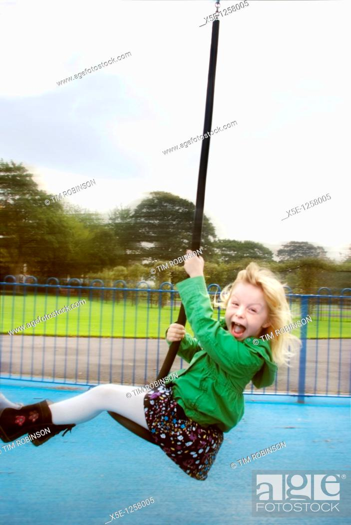 Stock Photo: 7 year girl swinging past on playground ride making a face.