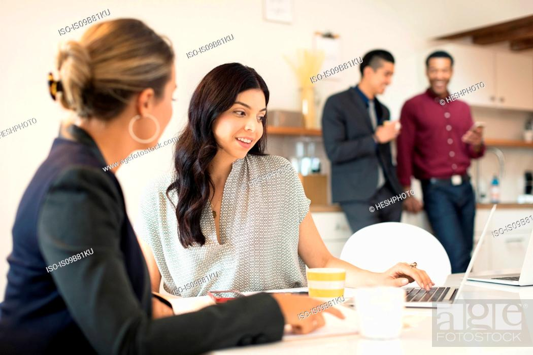Photo de stock: Two young businesswomen having meeting at desk.