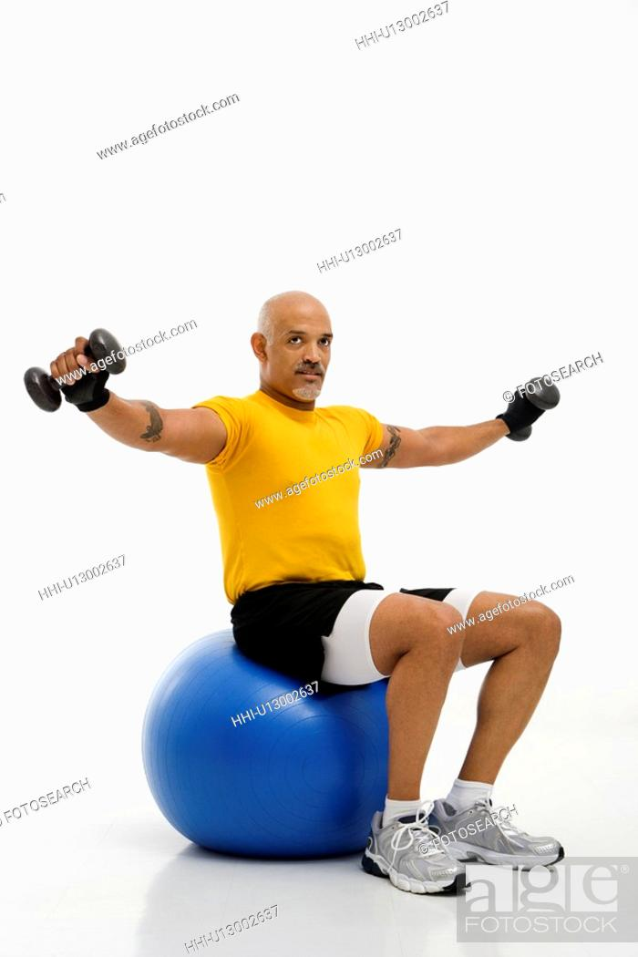 Stock Photo: Mid adult multiethnic man balancing on blue exercise ball with outstretched arms holding dumbbells and looking at viewer.