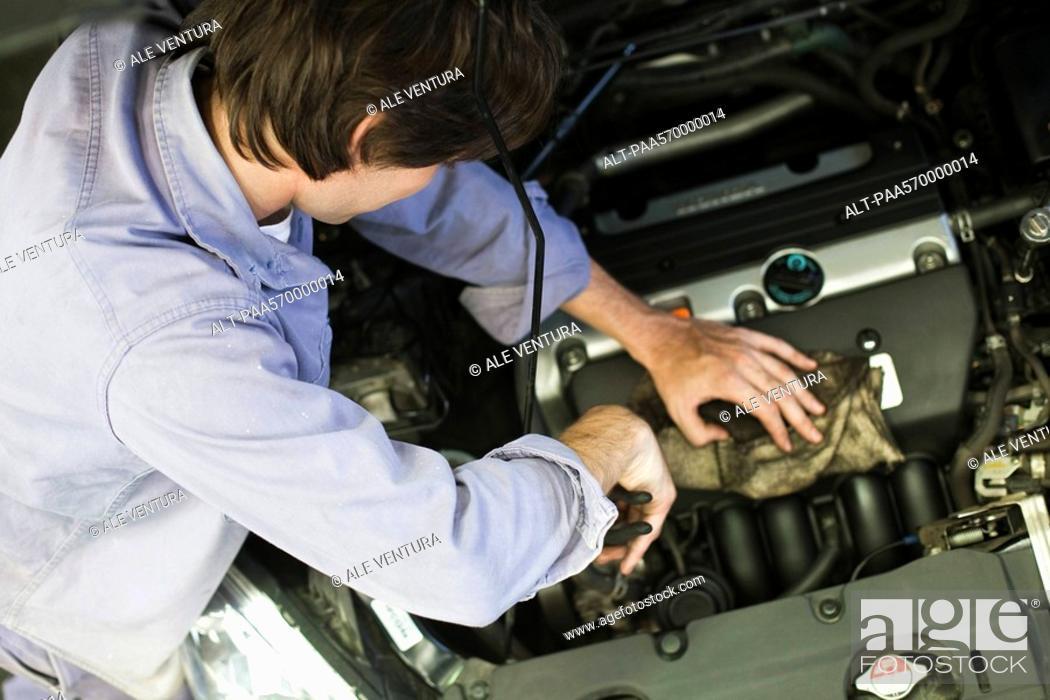 Stock Photo: Mechanic repairing car engine.