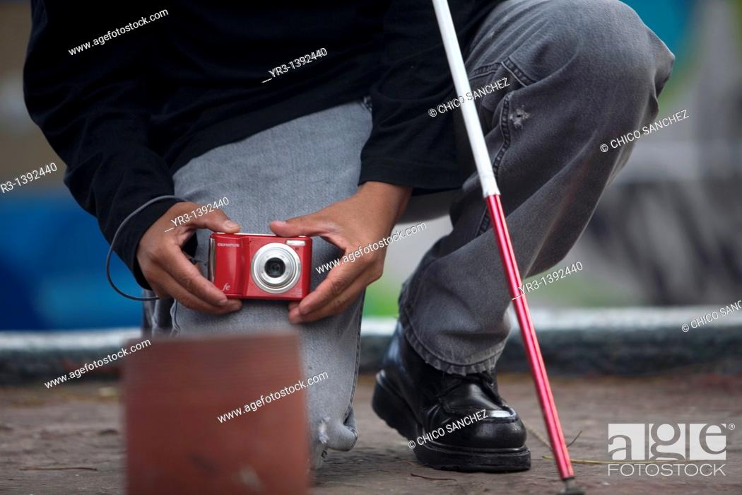 Stock Photo: A blind photographer takes pictures as he kneels.