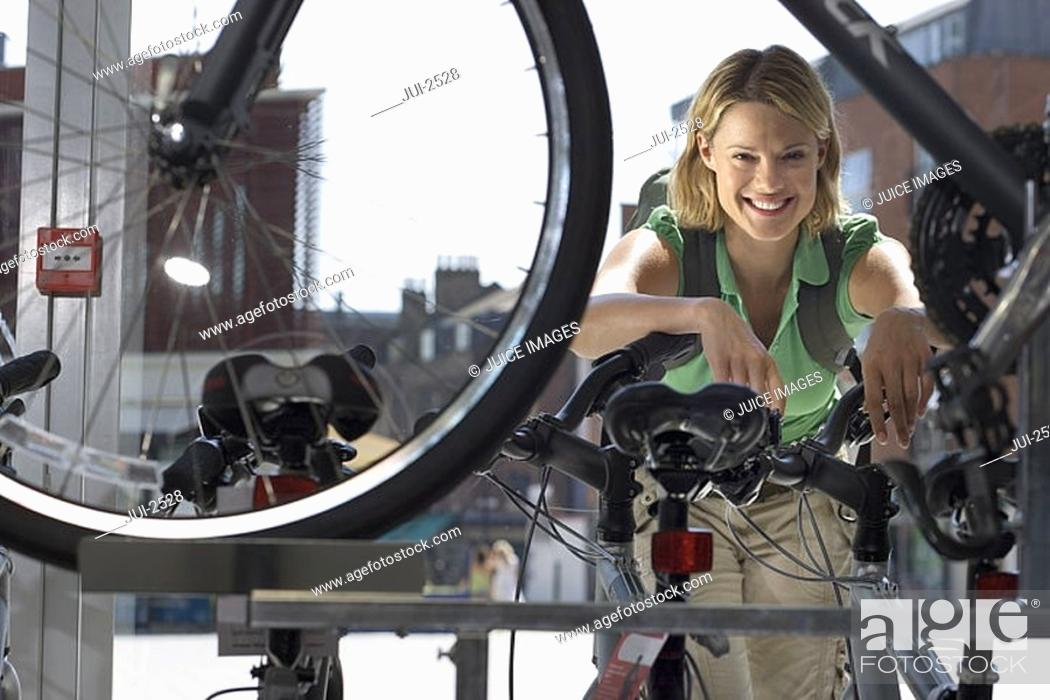 Stock Photo: Young woman shopping for new bike in bicycle shop, view through bike frame, smiling, portrait.