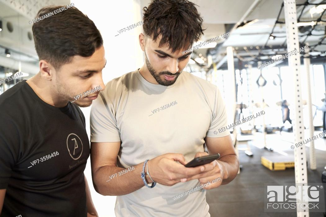 Stock Photo: Two men looking at smart phone in gym.