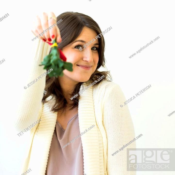 Stock Photo: Studio shot of woman holding Christmas wreath.