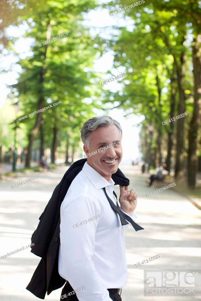 Stock Photo: Portrait of smiling businessman in park.
