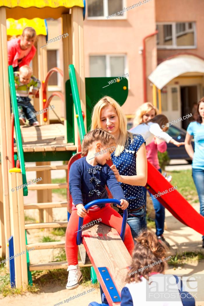 Stock Photo: Mother rocks her daughter on a seesaw at the playground.