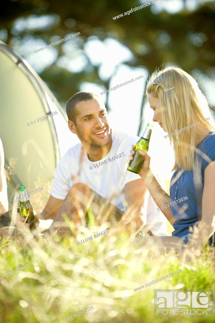 Stock Photo: A young couple sitting in front of a tent, drinking beer.