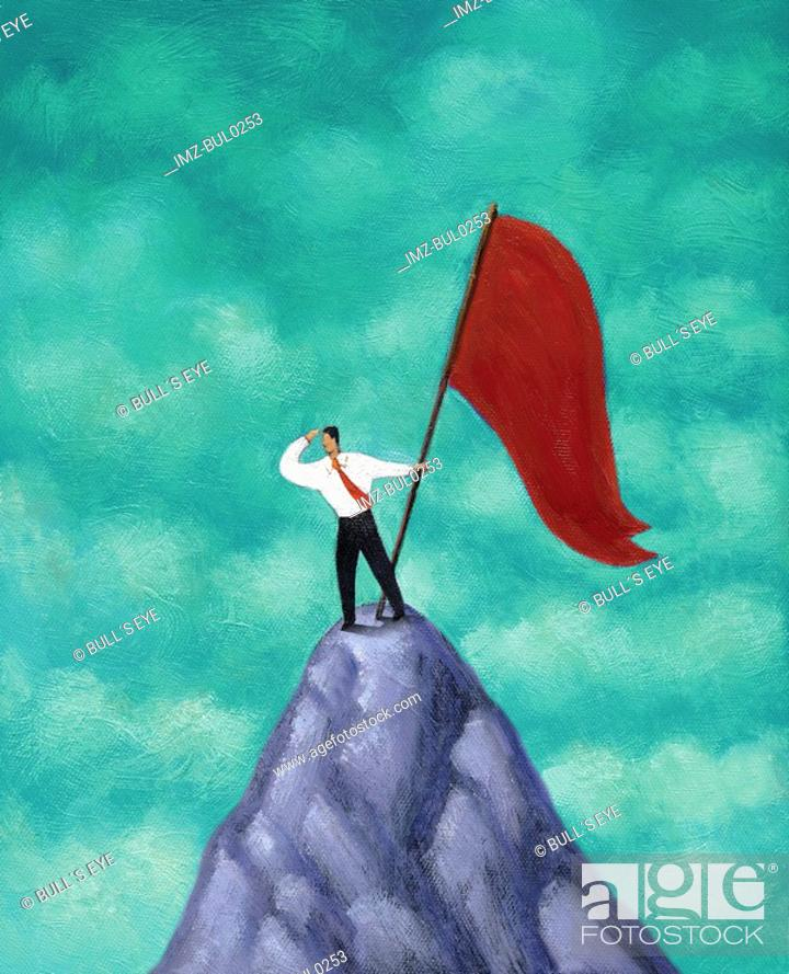 Stock Photo: Businessman standing with red flag on mountain peak, looking out into the distance.