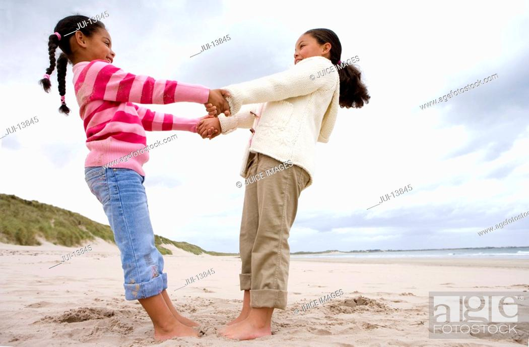 Stock Photo: Sisters 5-9 holding hands on beach, low angle view.