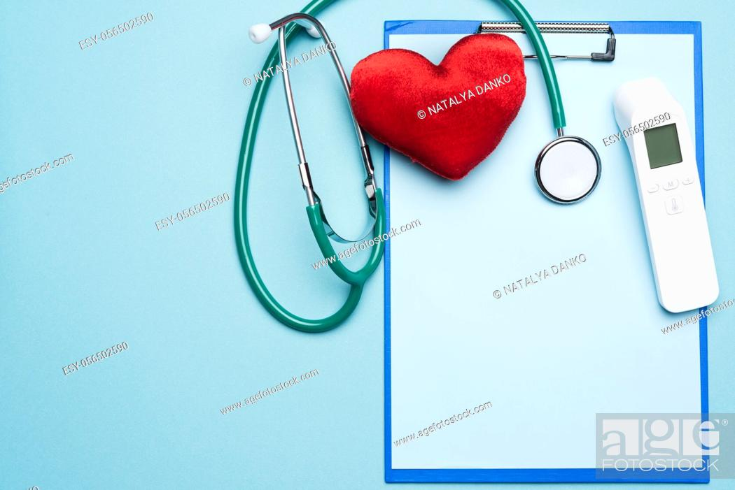 Stock Photo: red heart , electronic thermometer and other medical supplies on a blue background, top view.