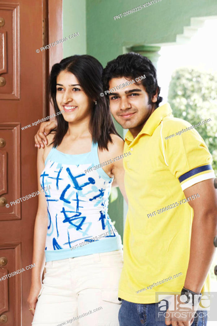 Stock Photo: Young couple standing at the doorway smiling.
