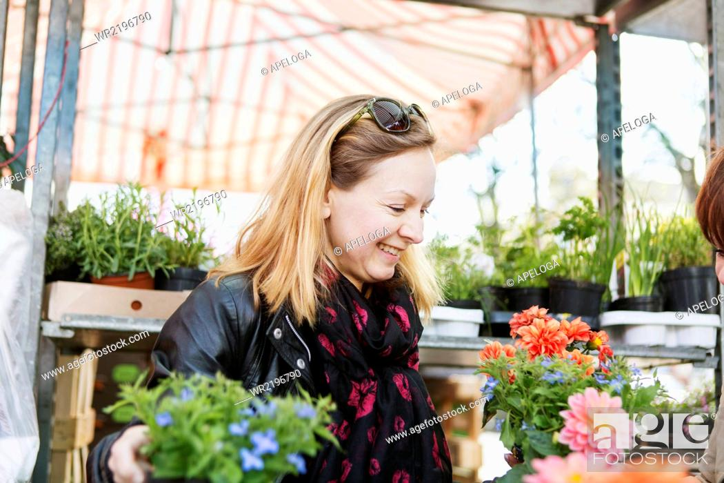 Stock Photo: Happy mature woman buying flower plants in nursery.